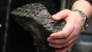 Suutari kiinnittää kenkiin nastoja.