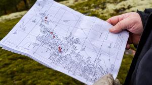En hand håller i en svartvit karta. Röda prickar har märkts ut på flera ställen på Käldö.