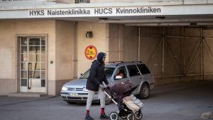 En kvinna med barnvagn utanför en byggnad. På bilden Kvinnokliniken i Helsingfors
