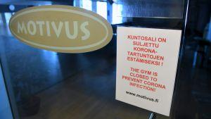 Motivus logo på en glasdörr. Bredvid en lapp om att gymmet är stängt.