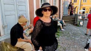 En kvinna står framför ett rosa hus och människor sitter bakom henne.