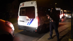 En beväpnad man står framför en polisbil