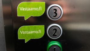 Knappar i en hiss. Gröna lappar tillhörande psykoterapicentret Vastaamo till vänster om siffrorna 2 och 3.