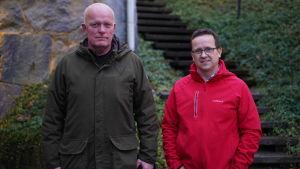 Två män står ute, ser in kameran. BAkom en trappa och vintergröna, marktäckande växter.