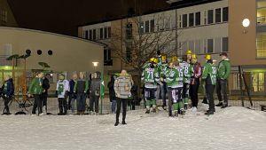 Flera personer i gröna skjortor och guldhattar står nära varandra, synbart glada. Några kramas.