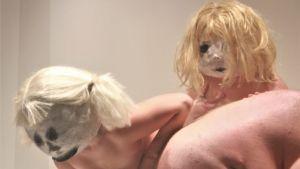 Tre nakna skådespelare i stora masker med blonda peruker står framåtlutade på en studioscen.