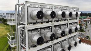 Rektangulär, silverfärgad maskin med flera cylinderformade luftintag med svarta lock.