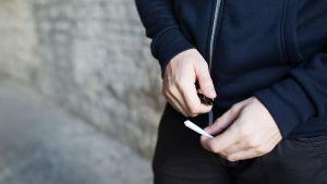 Anonym man med en cannabiscigarett i handen.