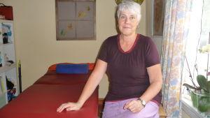 Agneta Westerlund vid sin privata mottagning. Sitter bredvid ett massagebord.