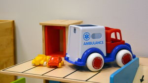 Två leksaksbilar och en leksaksambulans på ett bord.