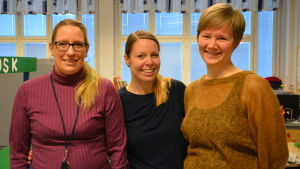 Tre kvinnor i ett klassrum.