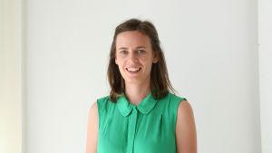 En kvinna med axellångt hår och en grön ärmlös blus. Hon står mot en vit vägg och tittar in i kameran.