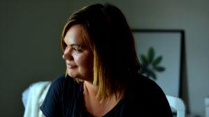 Kvinna i profil med mörkt hår i page. Hennes ansiktet lyses upp från ett fönster som inte syns i bild.
