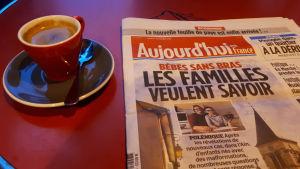En bild på en tidning, bredvid finns en röd kaffekopp.