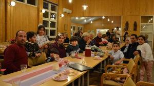 Två familjer sitter vid ett bord under en fest.