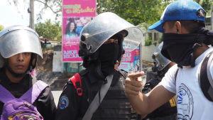 En ung demonstrant försöker förhandla med kravallpolis om att komma fram. I bakgrunden ett av otaliga enorma propagandaplakat med president Daniel Ortega och hustrun, vicepresident Rosario Murillo.