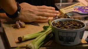 Närbild av en skål med trattkantarell och en hand som pressar vitlök med en kniv.
