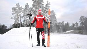 Niklas Westerlund i röd träningsdräkt står på skidspåret med skidor i handen.
