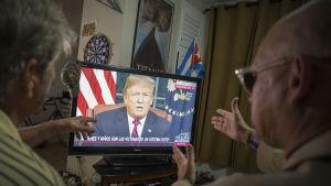 Två personer ses titta på Donald Trumps tal i en TV.