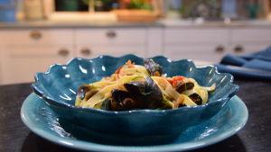 Portion med blåmusselpasta i ett kök
