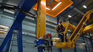 En person jobbar med hjälp av en skylift i en fabrik.
