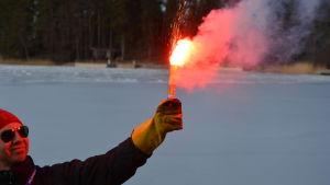 En man med röd mössa och solglasögon håller i ett nödbloss som brinner med en rödorange färg.