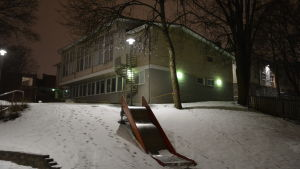Kärnhuset vid Sirkkala skola, en gul tvåvåningsbyggnad en snöig vinterkväll.