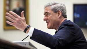 Arkivbild Robert Mueller, med utsträckt hand, vittnar i kongressen 2012