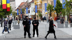 rumänska flaggor och EU-flaggor längs med en gågata i Sibiu. I förgrunden poliser. Det går människor på gatan.