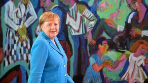 Angela Merkel framför en färgrann målning i Berlin 3 juli 2019.
