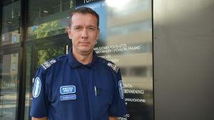 Polisen Stephan Sundqvist står framför en mörk vägg och ser in i kameran.