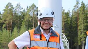 En man med skyddshjälm och orange väst står framför ett vindkraftverk.
