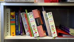 Kokböcker i en bokhylla.