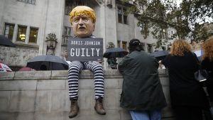 En demonstrant i fångdräkt och en Boris Johnson-mask sitter utanför Högsta domstolen i London.