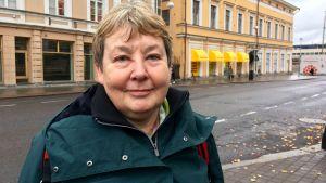 Merja Fredriksson poserar utomhus i höstväder. I bakgrunden syns ett gult hus.