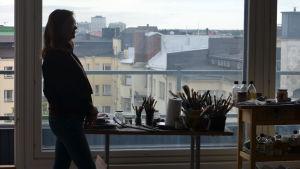 Målaren Magdalena Åberg vid stort fönster i motljus. i fönstret syns många hustak och himmel, på bordet framför fönstret penslar och färger