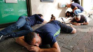 Israeler lade sig ner på marken för att ta skydd under en raketattack i Ashkelon, i södra Israel på onsdagen.