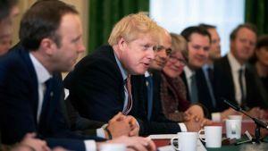 Boris Johnson sitter vid ett bord med sina regeringskolleger på bägge sidor.