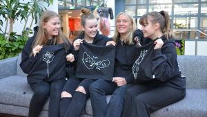 Fyra unga kvinnor sitter på en soffa och håller upp tygkassar med grafiskt tryck.