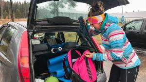 Kvinna sätter träningsväska in i bakluckan på bilen
