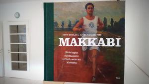 Pärmbild på boken Makkabi - Helsingin juutalaisen urheiluseuran historia. Pärmmotiv löparen Elias Katz.