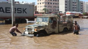 Tre pojkar försöker få loss en bil som fastnat i en översvämning.