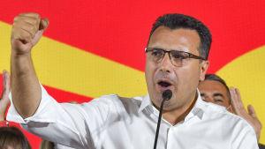 En man (Zoran Zaev) talar i mikrofon och har handen i en knytnäve upphöjd i luften.