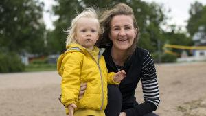 En kvinna och ett litet barn i gul jacka som tittar mot havet.