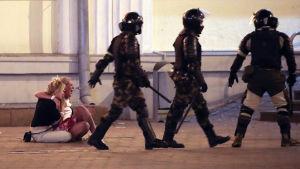 Belarusisk kravallpolis går förbi två skrikande kvinnor som sitter på gatan