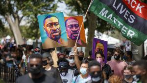 Mielenosoittajat Yhdysvalloissa kantavat poliisiväkivallan seurauksena kuollutta Goerge Floydia esittäviä värikkäitä kylttejä.