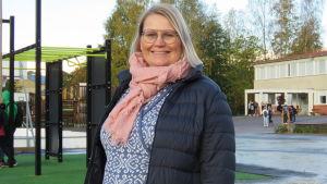 Porträttbild på Maria Lindberg, en kvinna med ljust, halvlångt hår, glasögon och svart, tunn dunjacka.  I bakgrunden en skolgård med elever. Höst.