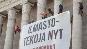 Mielenosoittajia Eduskuntatalon pylväissä.