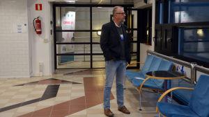Man med glasögon och svart kavaj står och tittar ut genom fönstret i Wasalines terminal.