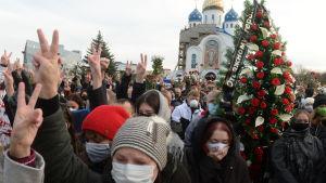 Människor som samlades till minnesceremonin för Bondarenko i fredags bar på blommor och visade segertecknet.